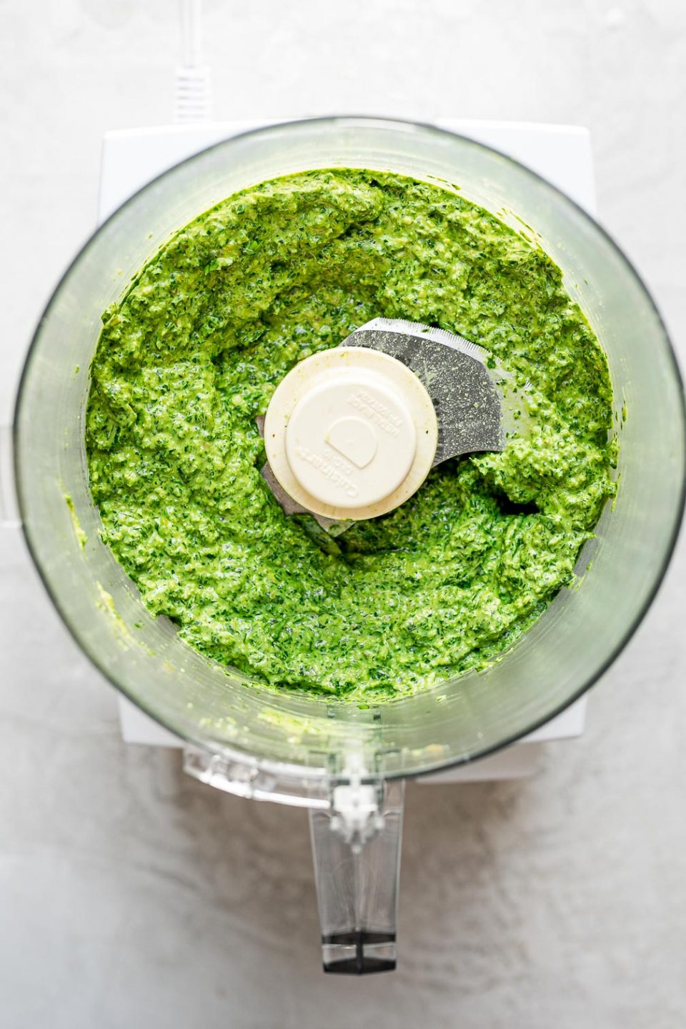 Blended green goddess pesto in a food processor carafe, atop a white surface.