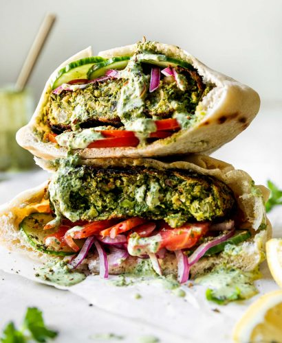 Two Grilled Falafel Burgers stacked on top of each other served inside a pita stuffed with a smear of hummus, thinly sliced tomatoes, cucumbers, & pickled red onion. The chickpea veggie burgers have then been drizzled with spicy green tahini sauce. The burgers are on a small piece of wrinkled parchment paper on top of a white surface, with a jar of tahini sauce and sliced lemons in the background & foreground.