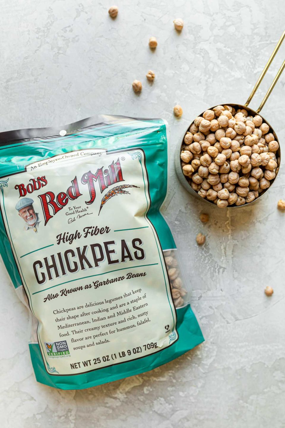 Grilled Falafel Burger staple ingredient arranged on a white textured surface: A package of Bob's Red Mill Dried Chickpeas rests on the surface with a measuring cup of dried chickpeas sitting alongside it, & loose dried chickpeas spread scattered around.
