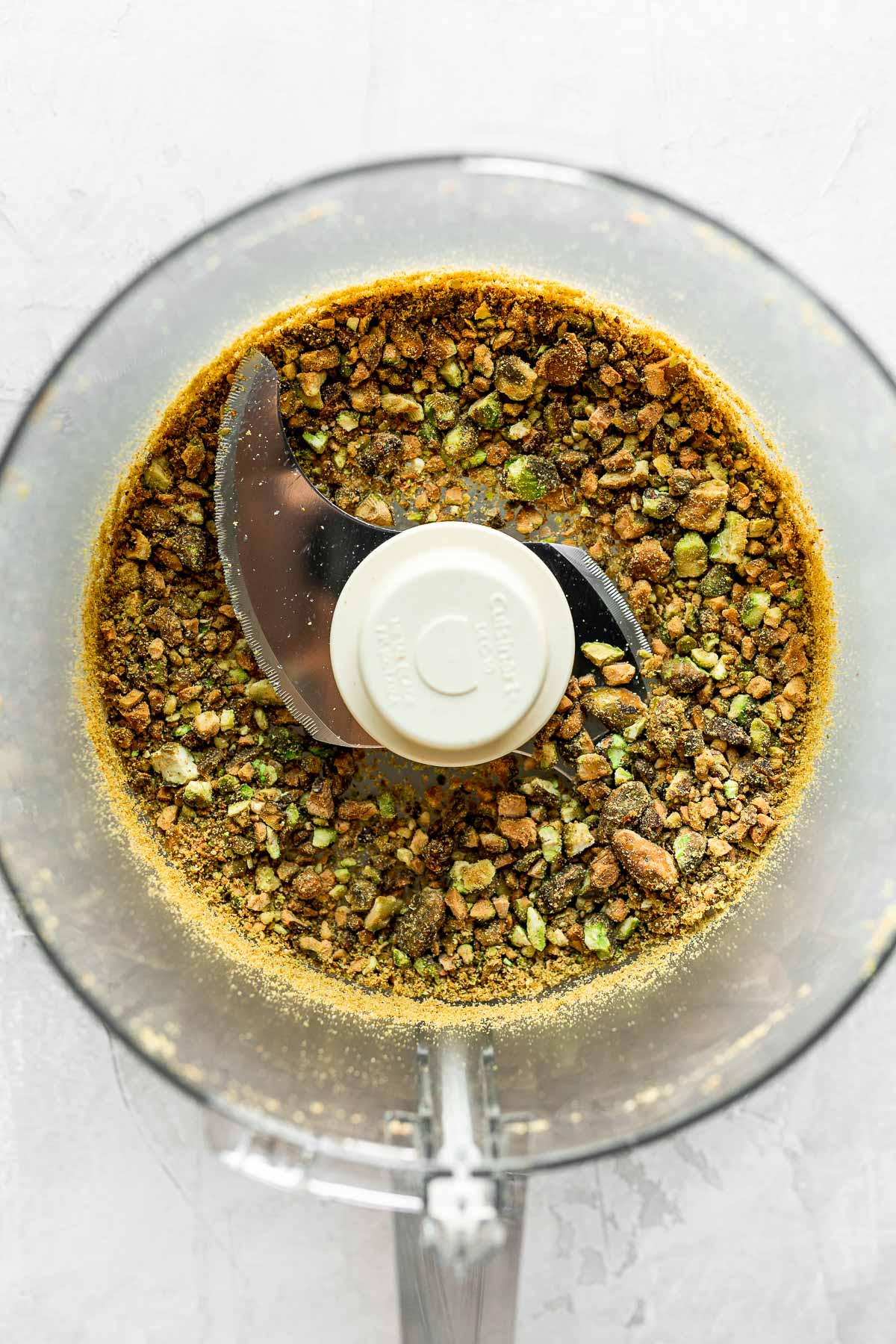 Roughly chopped pistachios & al dente cooked chickpeas combined a food processor. The food processor bowl sits on top of a white textured surface.