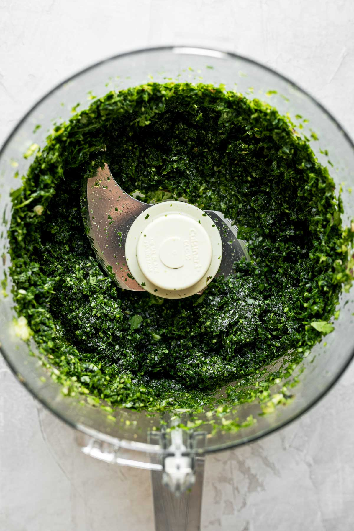 Onion, lemon zest, jalapeño, & fresh herbs finely chopped in a food processor. The food processor bowl sits on top of a white textured surface.