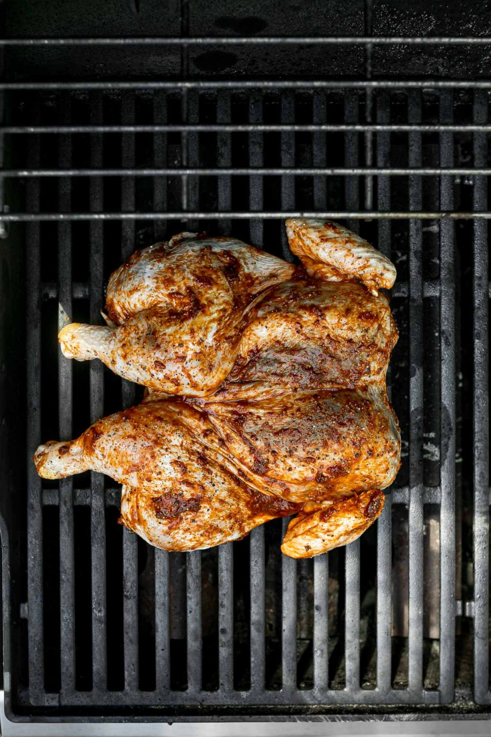 Spatchcocked/butterflied chicken on grill grates.