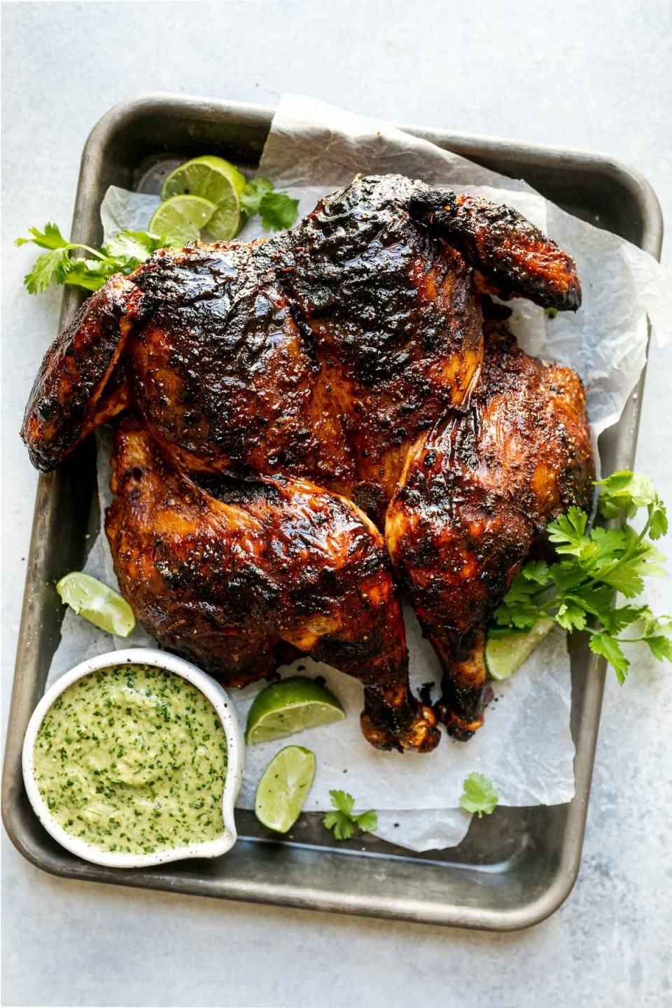 Grilled spatchcocked chicken with crispy, charred skin, sitting atop a parchment-lined baking sheet surrounded by lime wedges, fresh cilantro, & charred jalapeno sauce. The baking sheet sits atop a light blue surface.