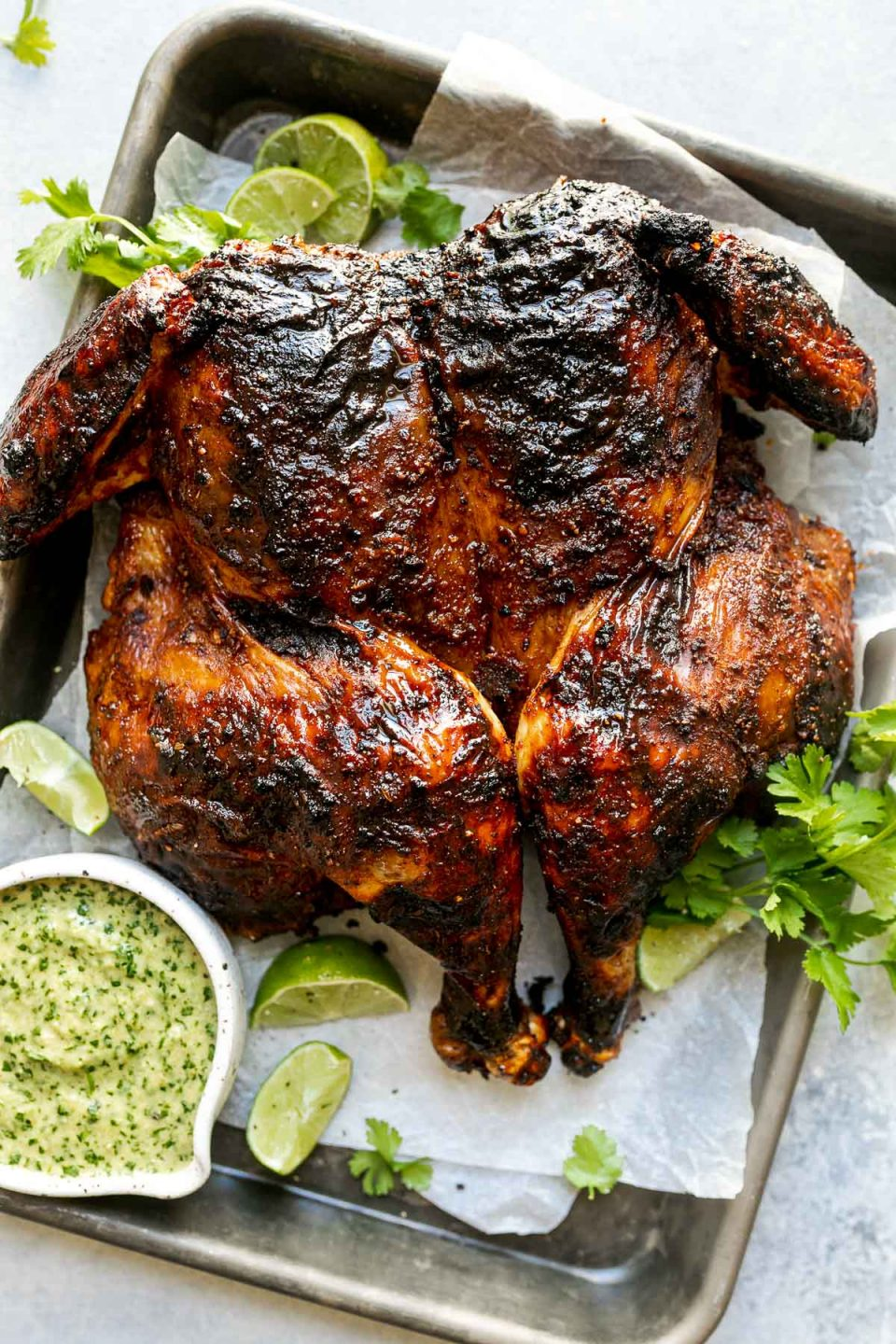Grilled spatchcocked chicken with crispy, charred skin, sitting atop a parchment-lined baking sheet surrounded by lime wedges, fresh cilantro, & charred jalapeno sauce. The baking sheet sits atop a light blue surface, surrounded by fresh cilantro leaves.