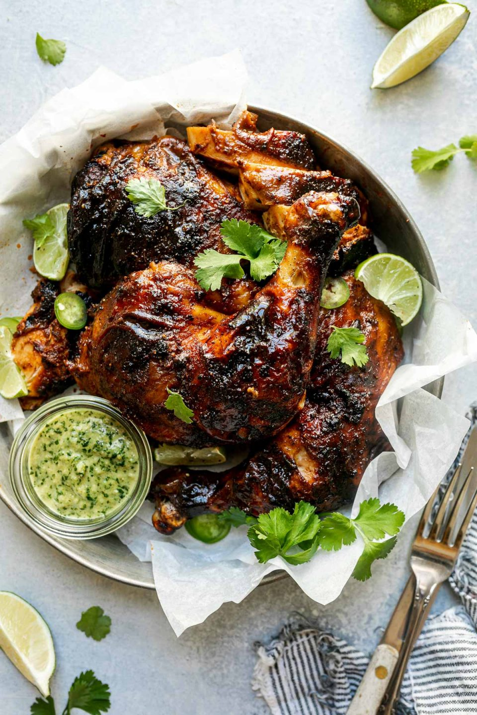 Butchered grilled whole chicken in a tin tray, topped with lime wedges, sliced jalapeno, & cilantro leaves. The tray sits atop a light blue surface, surrounded by fresh lime wedges, cilantro leaves, & a dark gray & white striped linen napkin.