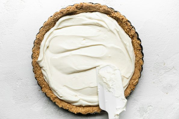 Pretzel graham cracker crust filled with no-bake cheesecake tart filling for no-bake summer berry tart, formed in a tart pan with removable bottom. A white rubber spatula smooths out the filling that is inside the crust.
