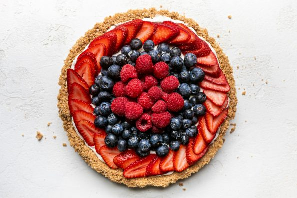 Close up of no-bake summer berry cheesecake tart with pretzel graham cracker crust. The tart is on a white textured surface, topped with fresh strawberries, blueberries, & raspberries. Surrounding the tart are a few pretzel & graham cracker crust crumbs.
