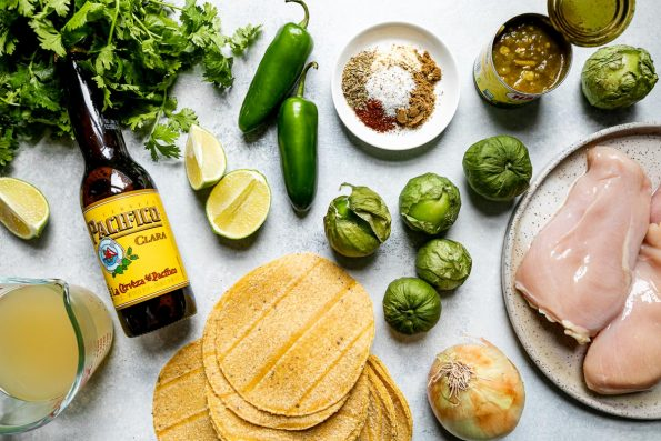 Homemade green chicken enchiladas ingredients arranged on a light blue surface – Cilantro, lime, chicken broth, Pacifico beer, corn tortillas, jalapeno peppers, spices, tomatillos, onion, chicken breasts & diced green chiles.