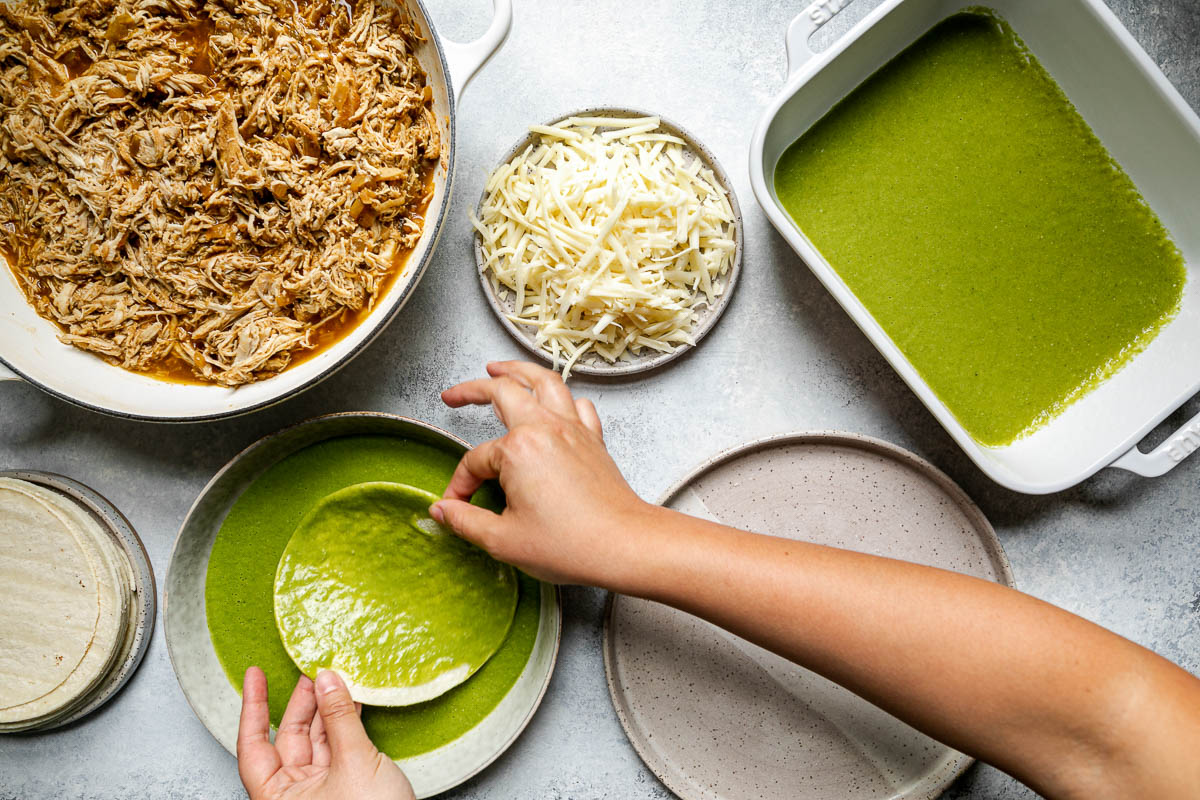 Green enchiladas assembly – green chicken enchiladas components (shredded chicken, shredded cheese, corn tortillas, & green enchiladas sauce atop a light blue surface. A woman's hands reach into the frame, holding a corn tortilla in a shallow bowl of green enchilada sauce to coat it before wrapping it with chicken & cheese.