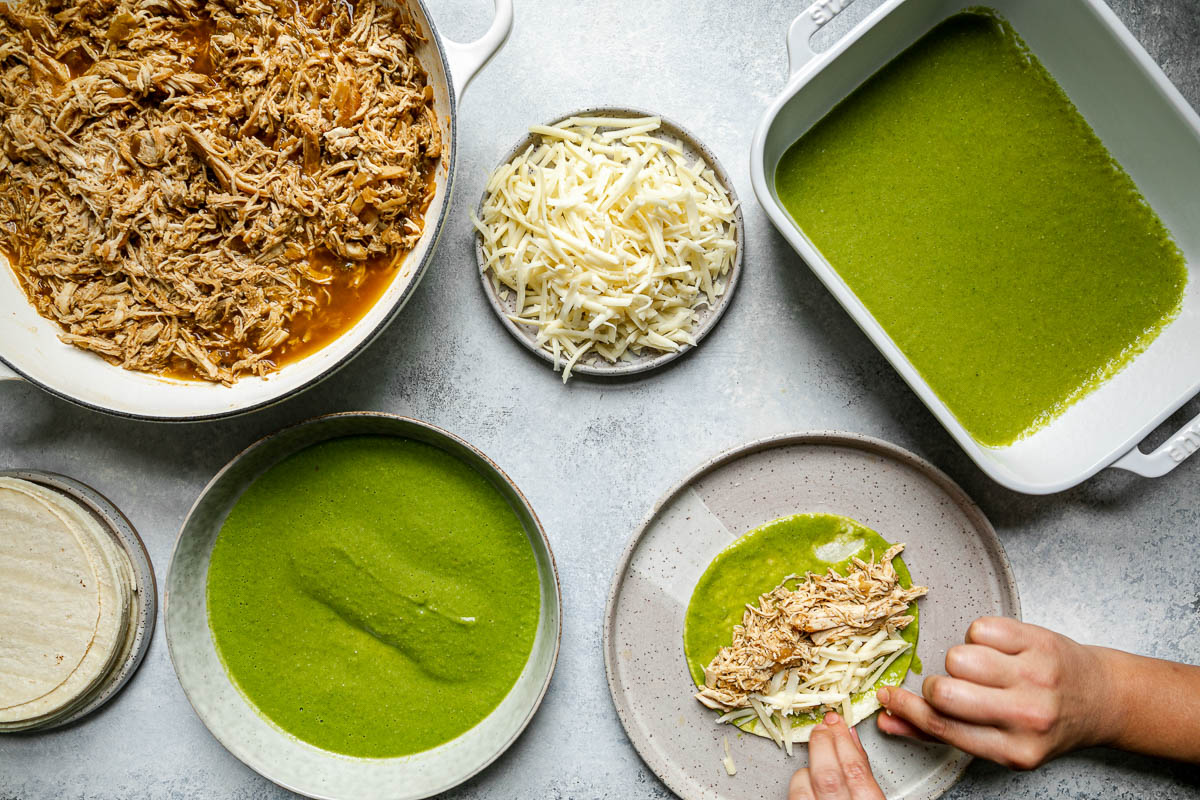 Green enchiladas assembly – green chicken enchiladas components (shredded chicken, shredded cheese, corn tortillas, & green enchiladas sauce atop a light blue surface. A woman's hands reach into the frame, wrapping chicken & cheese into a enchilada sauce-coated corn tortilla.