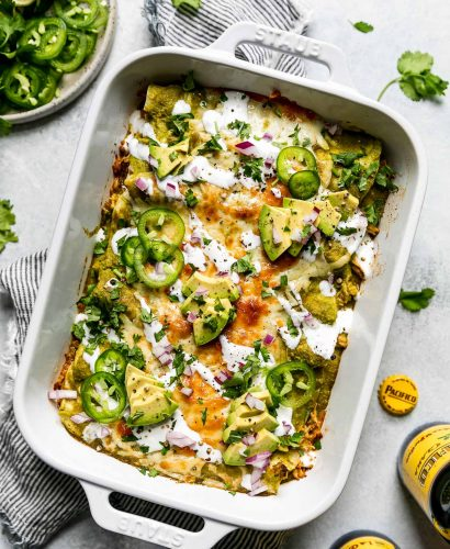Baked green enchiladas covered in cheeese, red onion, avocado, & sliced jalapeno. The baking dish sits atop a striped gray linen napkin on a light blue surface, surrounded by cilantro leaves, Pacifico beer, & a small plate of garnishes (lime wedges, cilantro, sliced jalapeno, etc.)