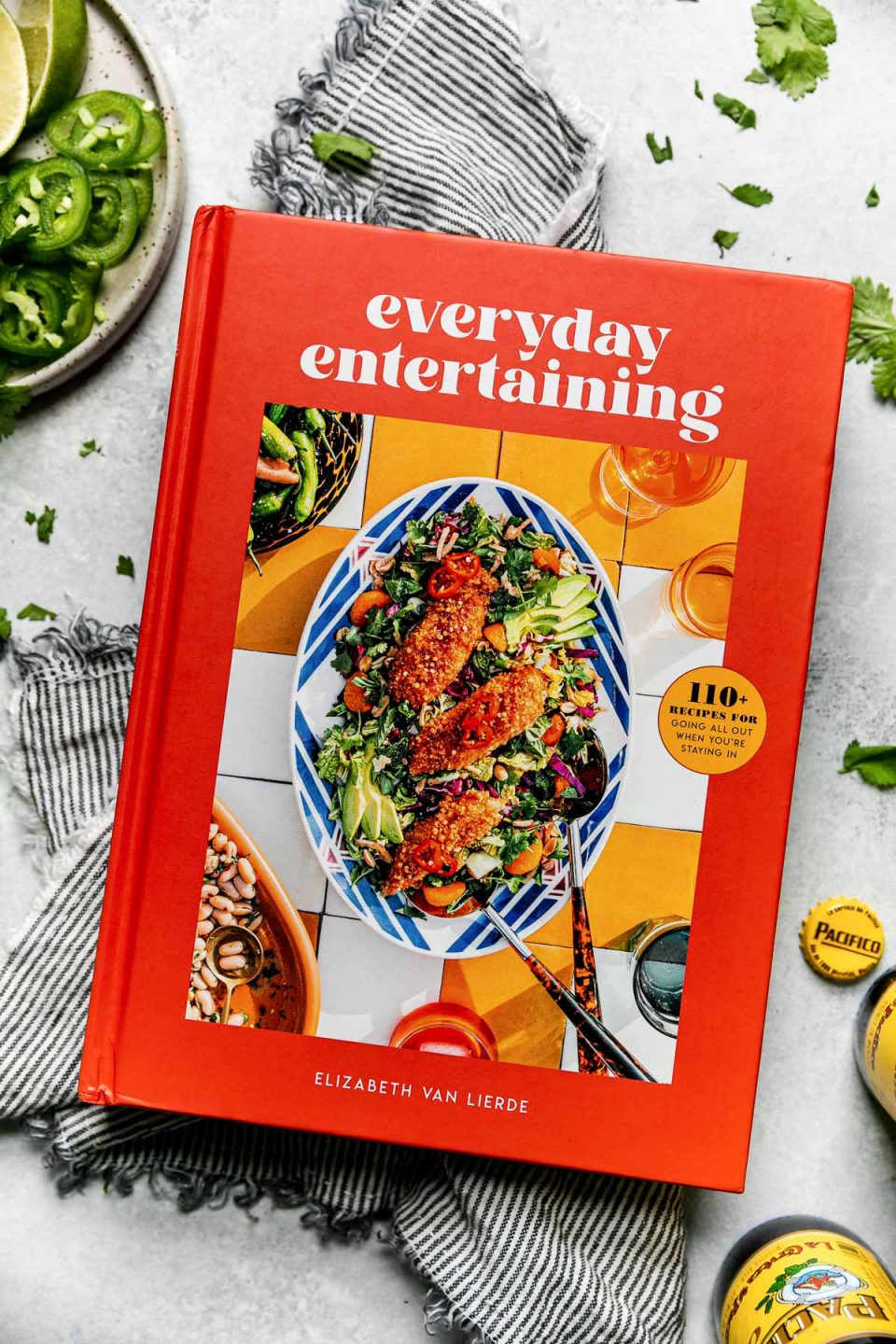 Everyday Entertaining, a cookbook by Elizabeth Van Lierde, atop a striped gray linen napkin on a light blue surface, surrounded by cilantro leaves, Pacifico beer, lime wedges, & a small plate of enchiladas garnishes (lime wedges, cilantro, sliced jalapeno, etc.)