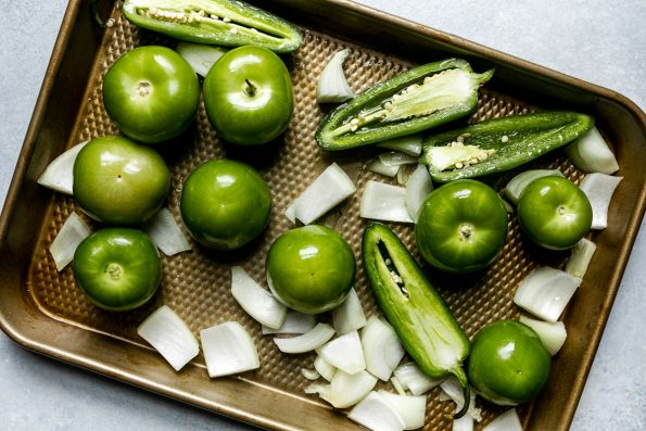 Homemade green enchilada sauce ingredients on a small sheet pan atop a light blue surface before roasting – tomatillos, halved peppers, & chopped onion.