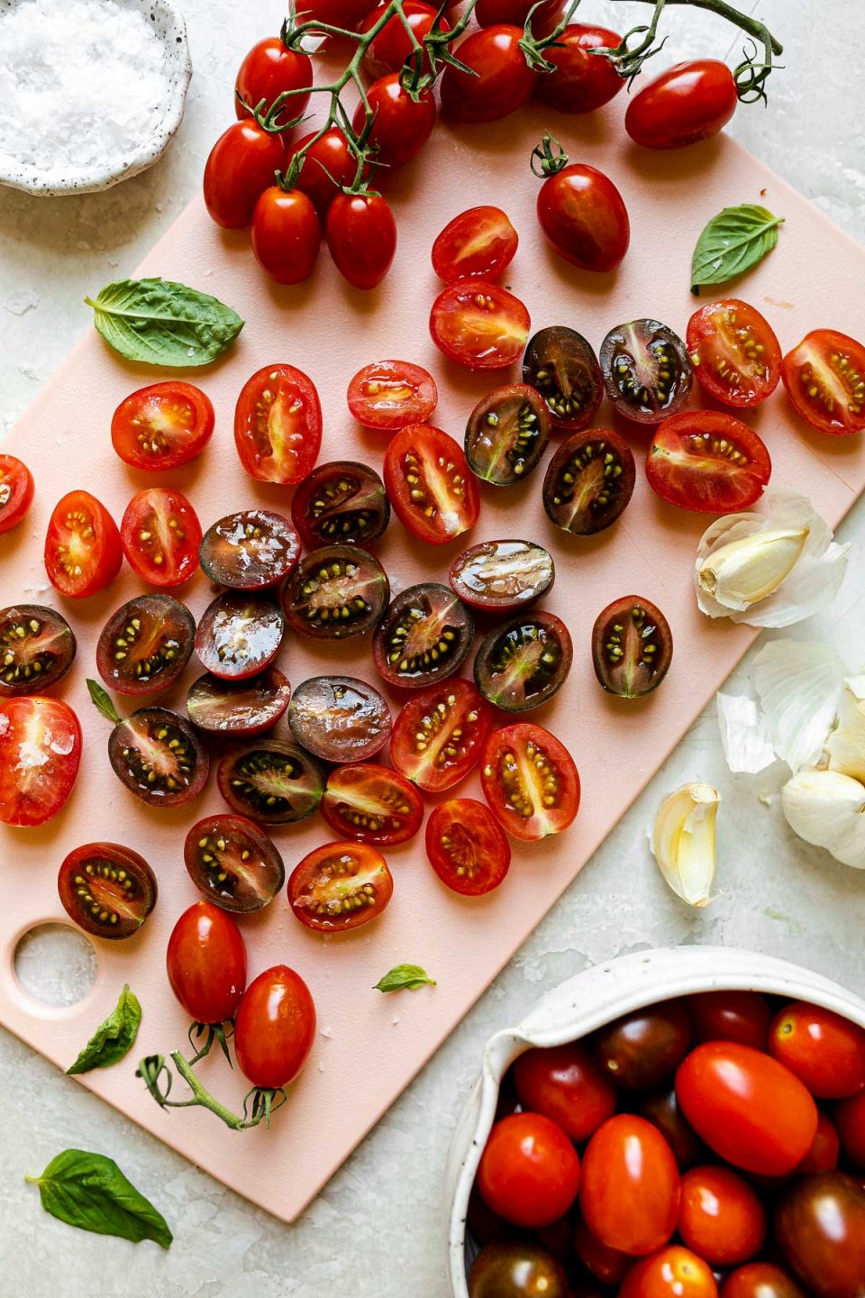 Top down view of halved cherry tomatoes arranged on a light pink cutting board. The cutting board sits atop a textured white surface surrounded by cherry tomatoes on the vine, a small bowl of whole cherry tomatoes, a few loose cherry tomatoes, a bulb of garlic with a few loose cloves, loose leaves of fresh basil, & a small pinch bowl filled with kosher salt.
