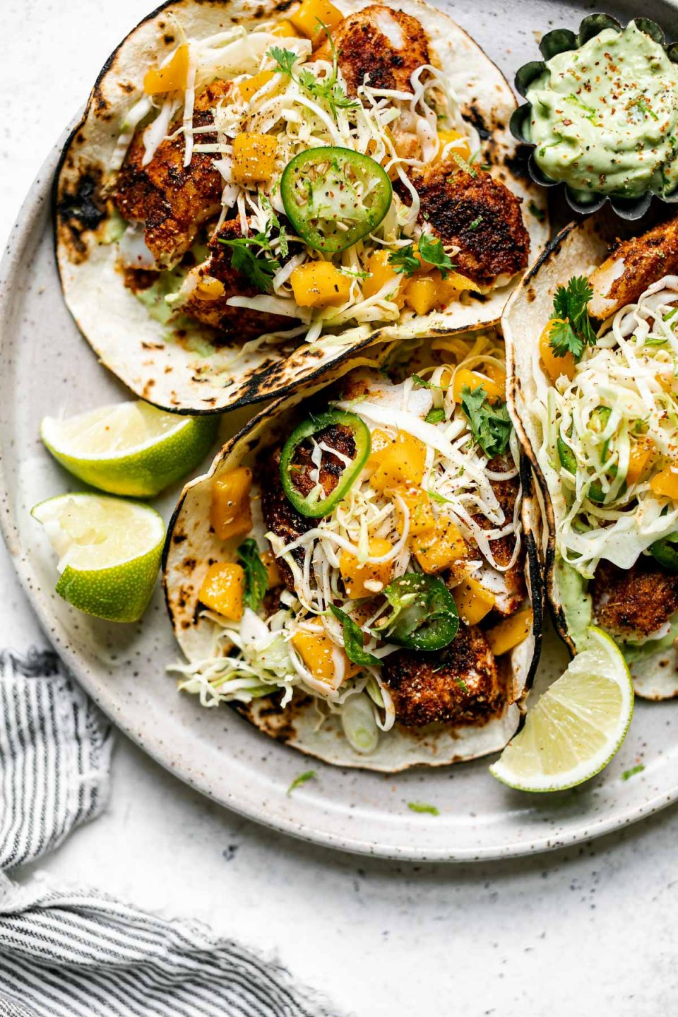 3 assembled grilled cod fish tacos topped with ginger mango slaw. The tacos sit atop a gray speckled ceramic plate with a small dish of avocado crema & lime wedges. The plate sits on a white surface, next to a gray and white striped linen napkin.