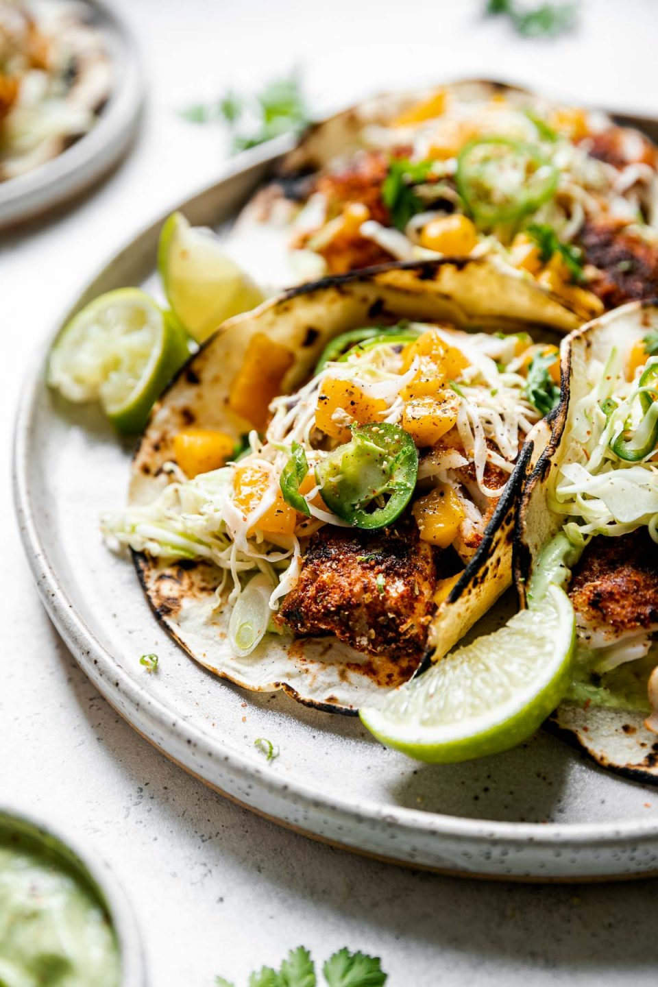 Side view of 3 assembled grilled cod fish tacos topped with ginger mango slaw. The tacos sit atop a gray speckled ceramic plate with a small dish of avocado crema & lime wedges. The plate sits on a white surface, next to a gray and white striped linen napkin.