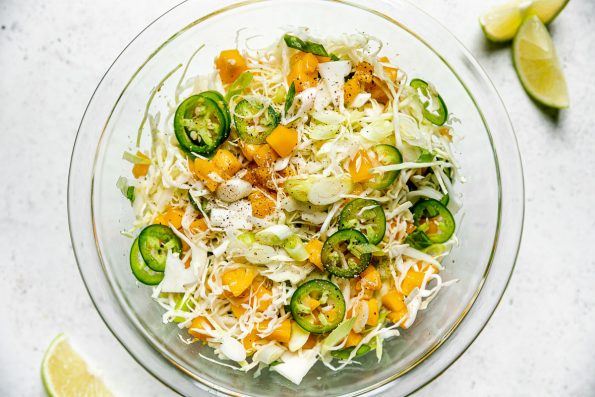 How to Make Grilled Cod Fish Tacos, Step 3: Ginger Mango Slaw tossed together in a glass mixing bowl. The bowl sits atop a white surface, next to lime wedges. The slaw is topped with thinly sliced jalapeno & a dusting of Tajín seasoning.