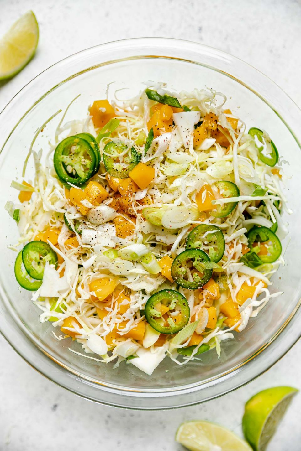 Fish Taco Slaw tossed together in a glass mixing bowl. The bowl sits atop a white surface, next to lime wedges. The ginger mango slaw is topped with thinly sliced jalapeno & a dusting of Tajín seasoning.