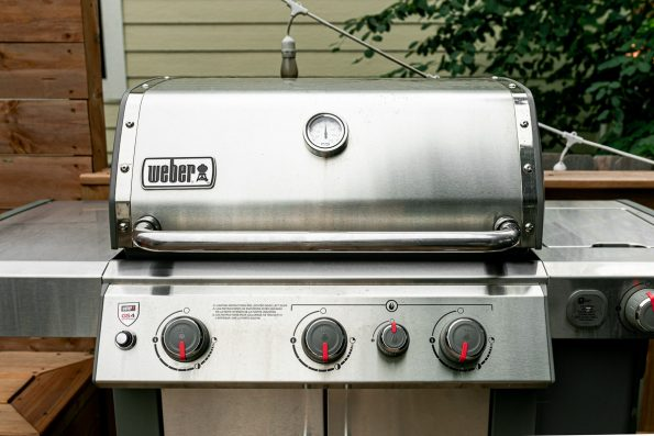 How to Make Grilled Cod Fish Tacos, Step 1: Weber Genesis II propane grill sits on a deck, preheated for medium-high direct heat grilling. A tree is in the background.