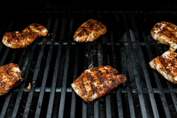 How to Make Grilled Cod Fish Tacos, Step 5: Seasoned cod fillets shown on grill grates, grilling for grilled fish tacos.