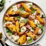 Grilled peaches, burrata cheese, fresh basil, & thinly sliced prosciutto arranged on a ceramic plate atop a textured white surface. Surrounding the grilled peach salad are fresh basil leaves, a small plate with arugula & grilled peach salad, a gray striped linen napkin, & large serving spoons.