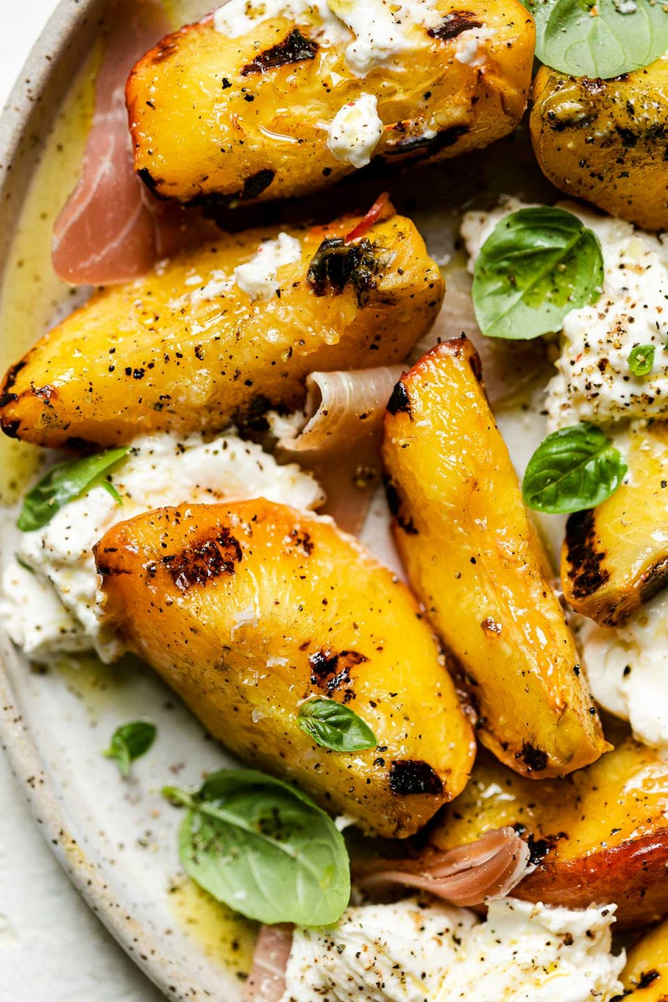 Close up of grilled peach burrata salad – grilled peaches, burrata cheese, thinly sliced prosciutto, & fresh basil leaves topped with flaky salt & freshly cracked pepper.