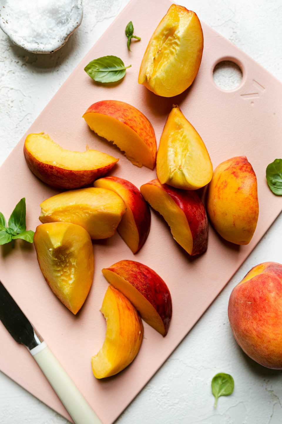Sliced peaches on pink cutting board atop a textured white surface. The peaches are surrounded by fresh basil leaves, a small bowl of flaky salt, & a small paring knife.