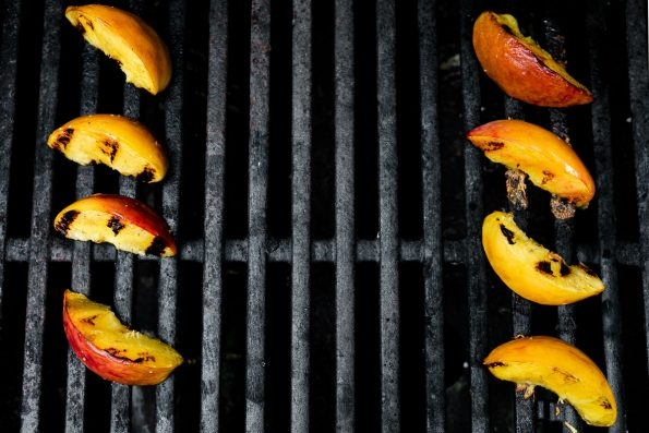 Grilled peach slices directly on grill grates.
