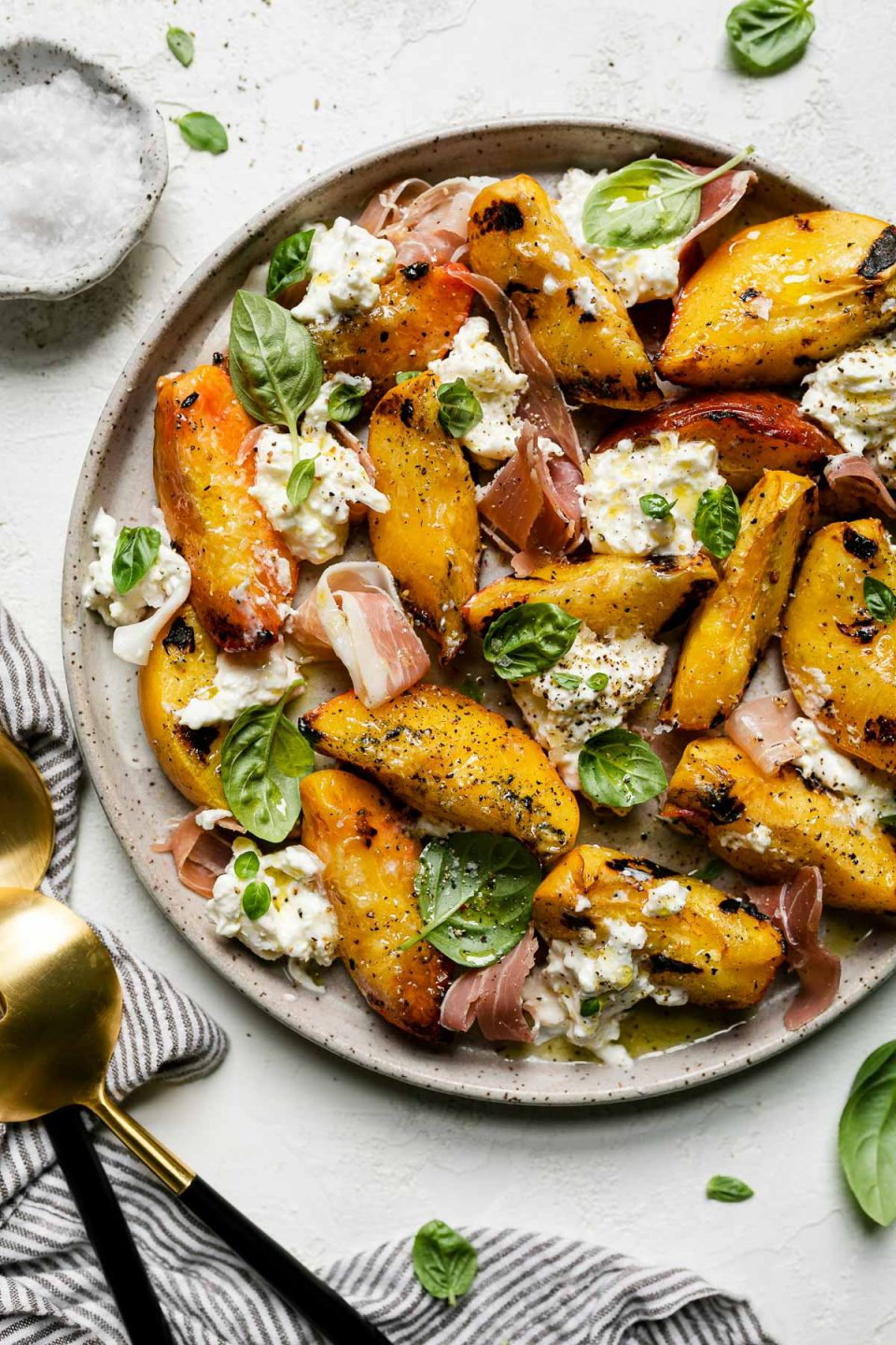 Grilled peaches, burrata cheese, fresh basil, & thinly sliced prosciutto arranged on a ceramic plate atop a textured white surface. Surrounding the grilled peach salad are fresh basil leaves, a small bowl of flaky salt, a gray striped linen napkin, & large serving spoons.