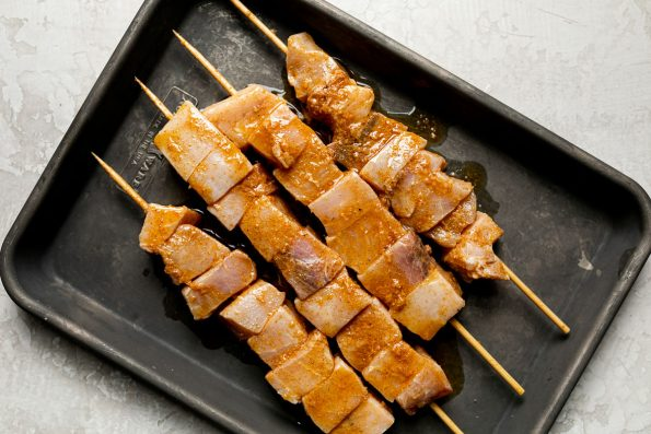 Marinaded cubed swordfish threaded on 4 bamboo skewers sitting in a dark gray baking sheet atop a creamy cement surface.