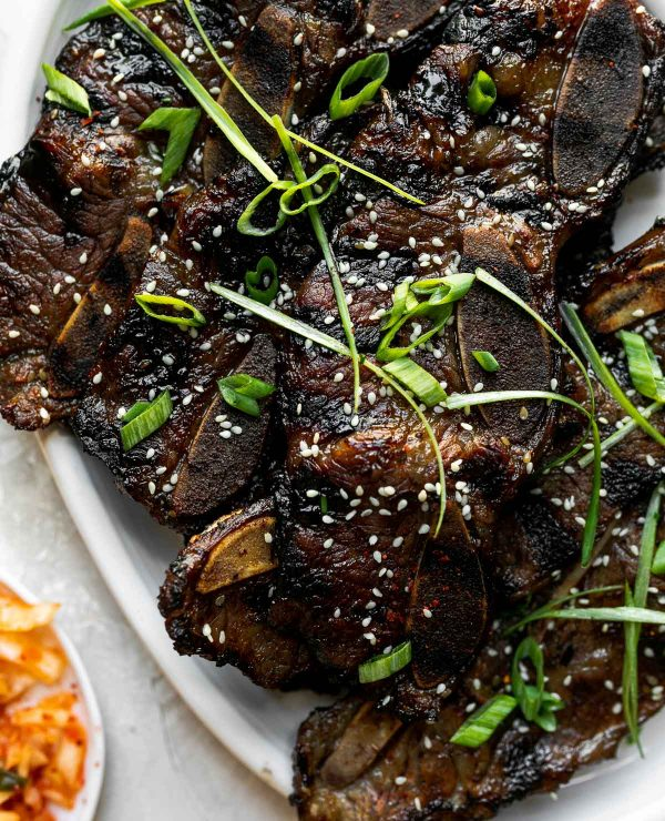 Kalbi beef short ribs on a white serving plate, topped with sesame seeds & thin sliced green onions. The platter sits atop a cement surface, surrounded by small plates of kimchi & rice.