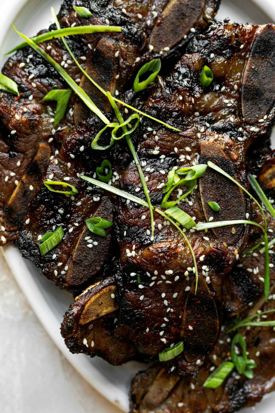 Kalbi beef short ribs on a white serving plate, topped with sesame seeds & thin sliced green onions. The platter sits atop a cement surface.