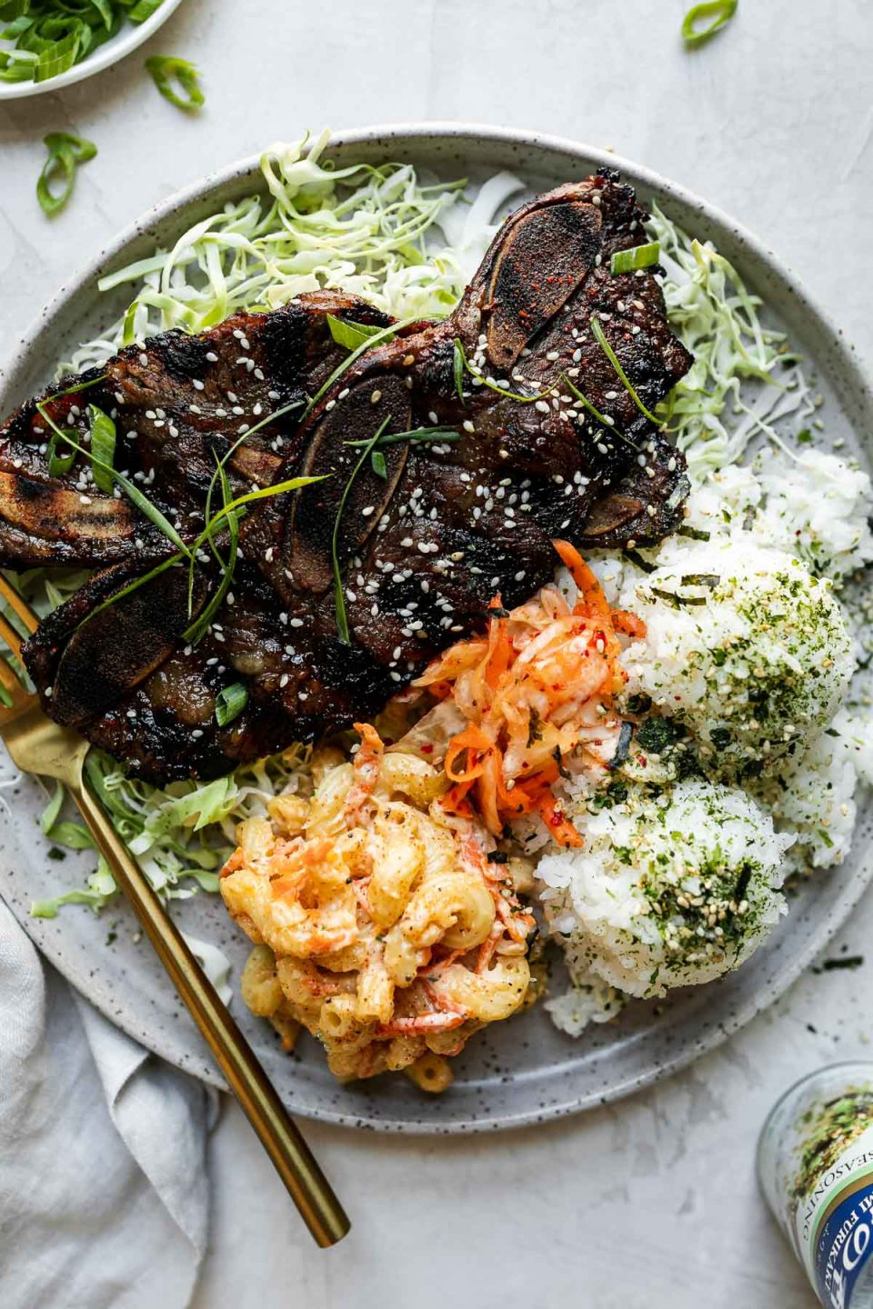 Kalbi served local Hawaiian-style, plated with shredded cabbage & scoops of rice, mac salad, & kimchi. The plate sits atop a cement surface alongside a second plate of kalbi, nori furikake seasoning, a gray linen napkin, & a plate of thin sliced green onions.