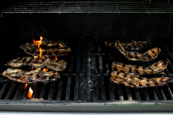 Korean beef short ribs on grill grates, grilling over direct flame.