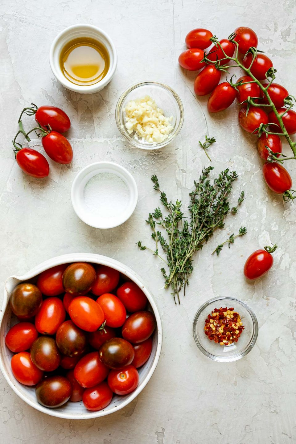 Slow roasted cherry tomatoes ingredients on a white textured surface: cherry tomatoes, olive oil, kosher salt, minced garlic, fresh herbs, & red pepper flakes.
