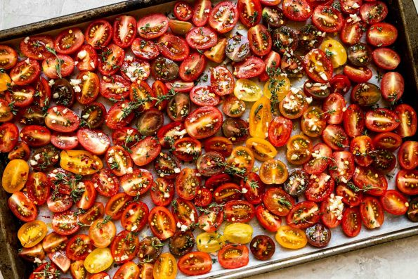 Raw cherry tomatoes arranged on a sheet pan lined with white parchment paper - sprinkled with fresh herbs & garlic ready to be slow roasted. The sheet pan rests on top of a light gray colored textured surface.