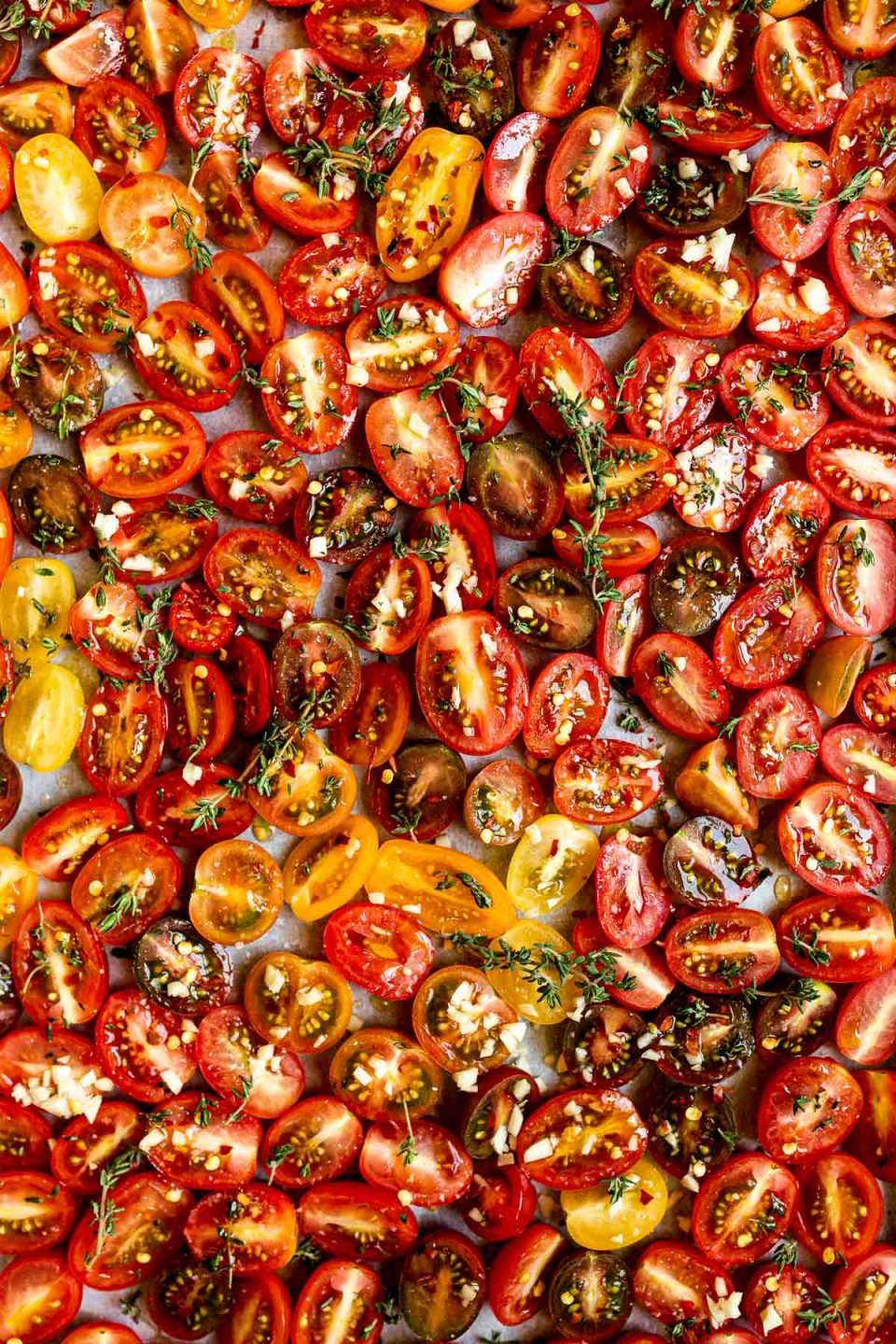 Raw cherry tomatoes arranged on a sheet pan lined with white parchment paper - sprinkled with fresh herbs & garlic ready to be slow roasted.