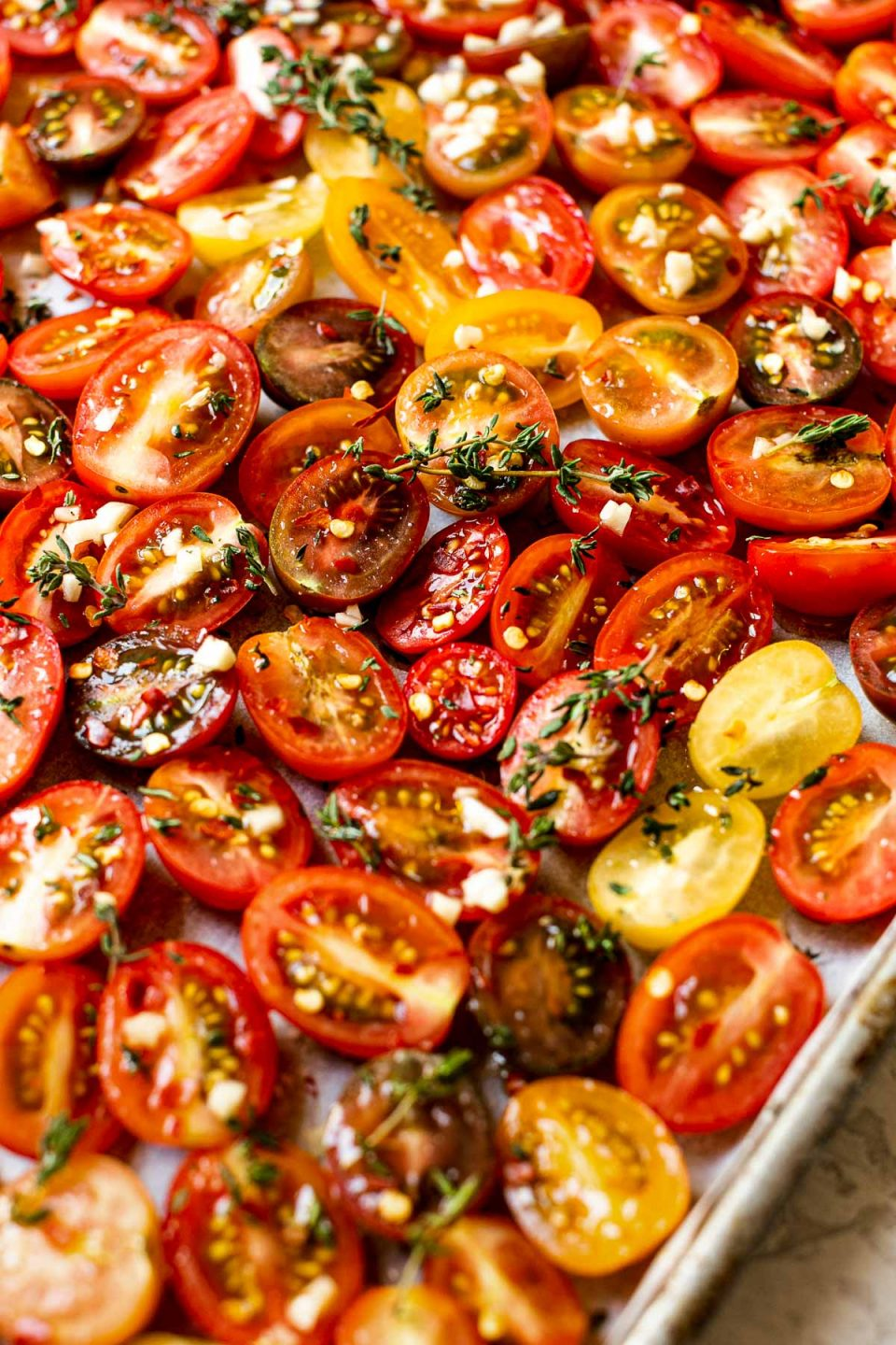 A close up & angled shot of raw cherry tomatoes arranged on a sheet pan lined with white parchment paper - sprinkled with fresh herbs & garlic ready to be slow roasted.
