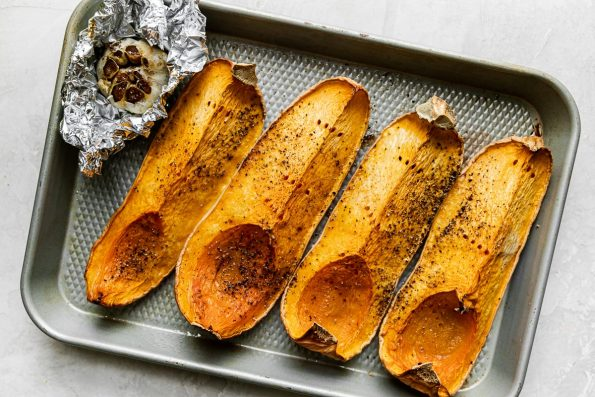 Four quartered & roasted butternut squash pieces arranged on a sheet pan alongside a bulb of roasted garlic wrapped in tin foil. The sheet pan rests on a creamy cement surface.