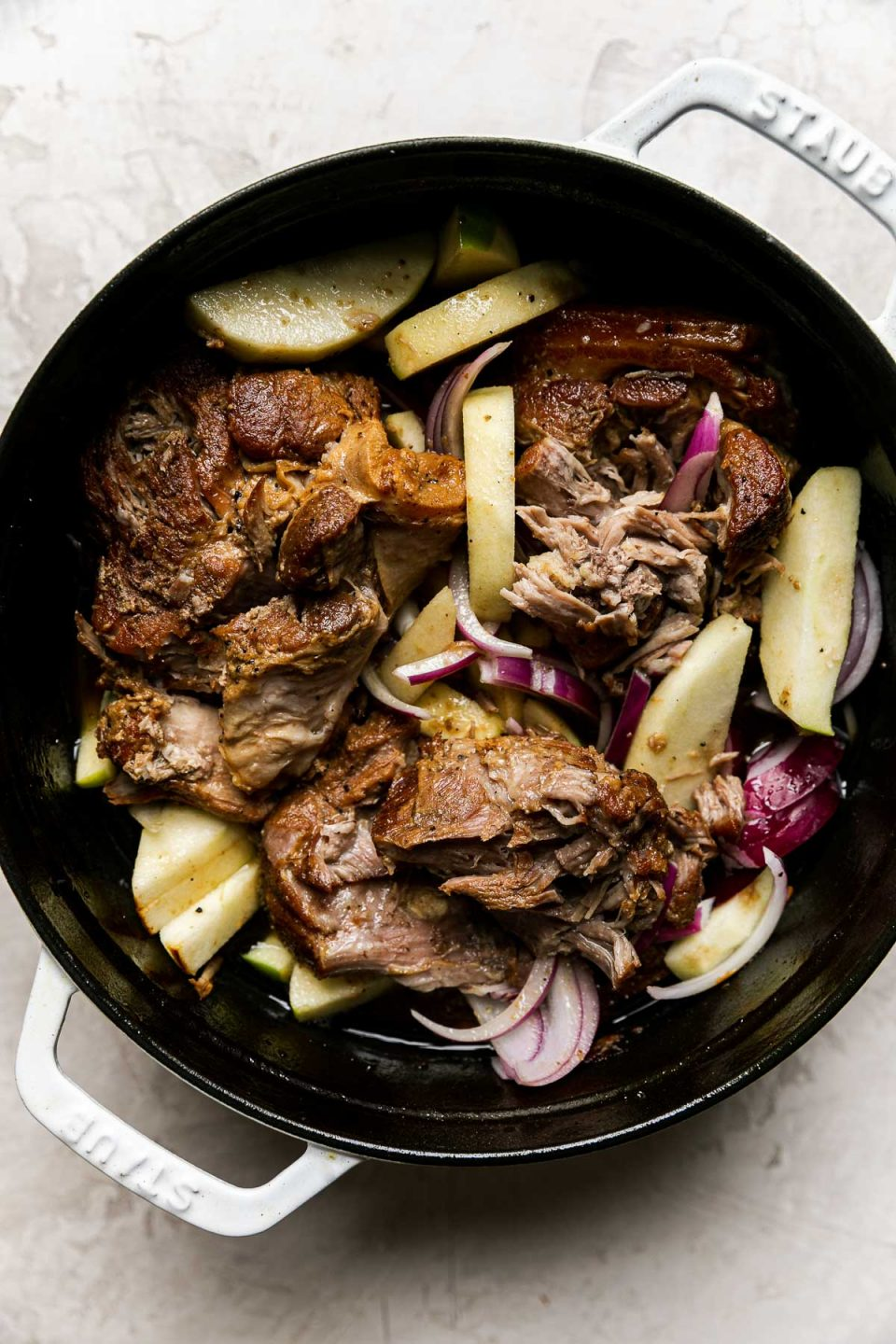 Apple Cider Braised Pork Shoulder, with apples & red onions added, in a white Dutch oven atop a creamy cement surface.
