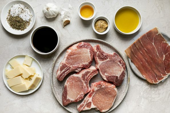 Grilled Stuffed Pork Chops ingredients arranged on a creamy cement surface – salt, balsamic vinegar, garlic, sliced asiago cheese, bone-in pork chops, pure maple syrup, Dijon mustard, olive oil, & thinly sliced prosciutto.