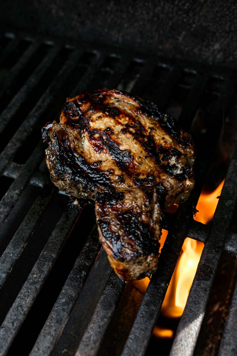 Bone in pork chop atop grilling grates with small flame flaring up through the grates.
