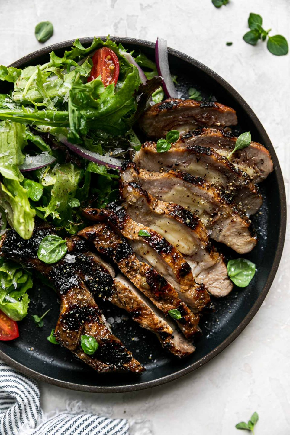 Grilled stuffed pork chop on a black plate. The pork chop is sliced, revealing its cheese & prosciutto filling. It's plated with a fresh green salad with tomatoes & red onions. The plate sits atop a creamy cement surface with a few sprigs of fresh oregano & a striped linen napkin.