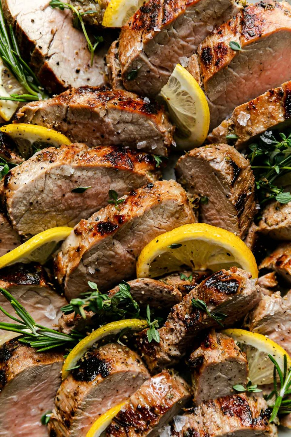 A close up of Lemon Garlic Grilled Pork Tenderloin. The tenderloin is sliced in medallions and garnished with sprigs of fresh rosemary, thyme, & lemon quarters for serving.