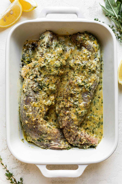 Two pork tenderloins soak in a homemade lemon garlic marinade in a white ceramic baking dish atop a creamy cement surface. Lemon wedges & sprigs of fresh herbs surround the baking dish.