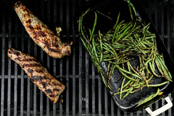 An overhead shot of two Lemon Garlic Grilled Pork Tenderloins & a grill basket filled with char-grilled green beans rest on a gas grill atop the grill grates.