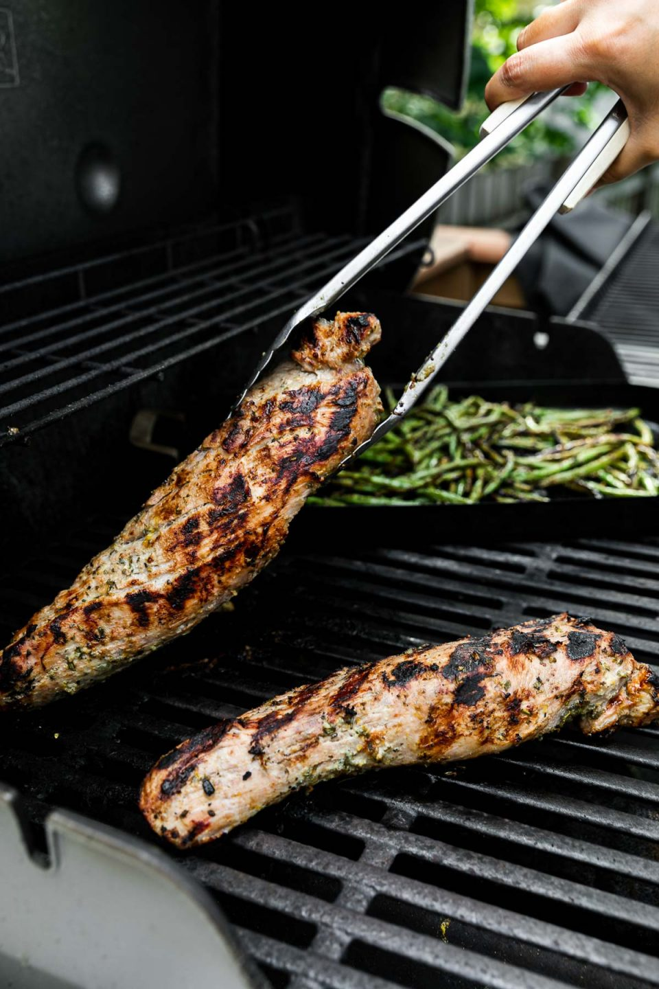 Two Lemon Garlic Grilled Pork Tenderloins on a gas grill. A woman's hand holds a set of grill tongs & is picking up one of the tenderloins to flip it on the grill grates. A grill basket rests on the grill grates in the background with char-grilled green beans cooking.