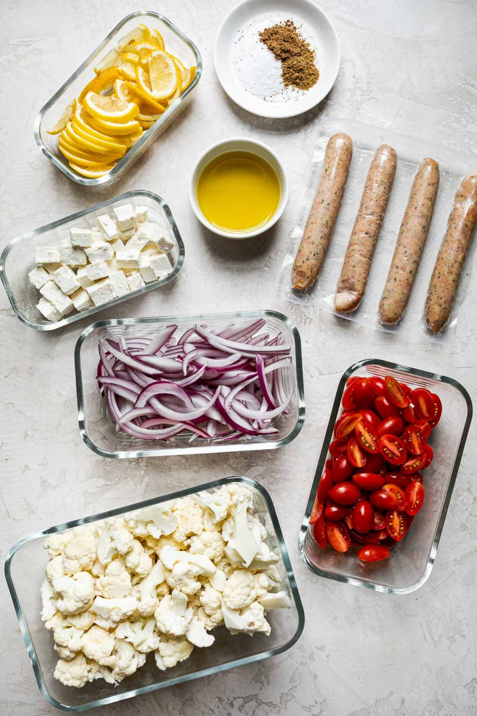 Sheet Pan Chicken Sausage and Veggies ingredients arranged on a creamy cement surface. The chicken sausage links are in their plastic wrapping. Cauliflower florets, tomatoes, sliced red onion, cubed feta, & sliced lemon are in glass Zwilling Fresh & Save storage containers. Olive oil is in a small bowl & spices are on a small white plate.