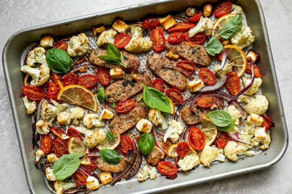 Baked Sheet Pan Chicken Sausage and Veggies on a silver quarter sheet pan atop a creamy cement surface. The sheet pan is topped with fresh basil leaves & ground black pepper.