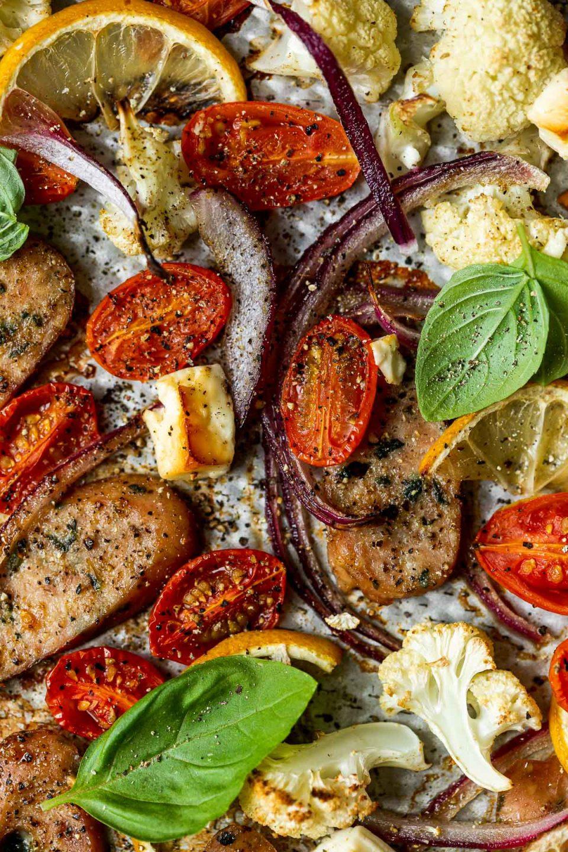 Macro shot of baked Sheet Pan Chicken Sausage and Veggies ingredients, topped with cracked pepper & fresh basil.